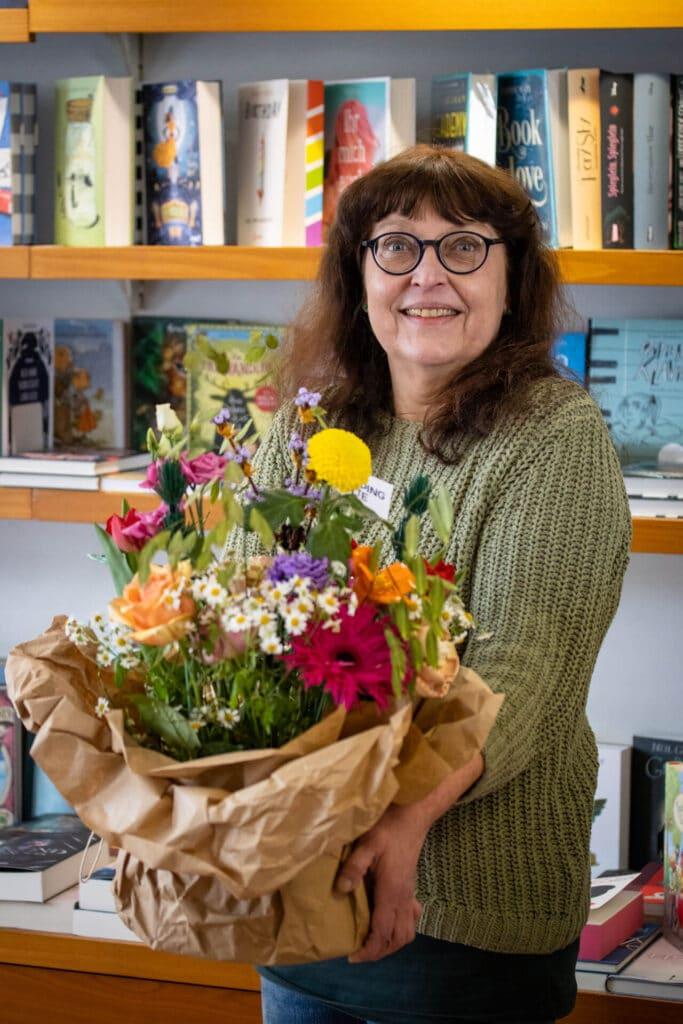 Frau Hiltrud mit ihrem Blumenstrauß vor ihren Bücherregalen